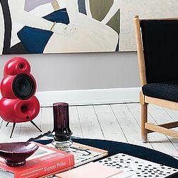 ein roter Podspeaker Bigpod steht auf dem Fußboden zwischen zwei Sofas