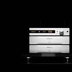 Man sieht eine komplette Streaminganlage bestehend aus einem Auralic Altair und zwei Endstufen Auralic Merak. Die Geräte sind schön ausgeleuchtet vor einem schwarzen Hintergrund.