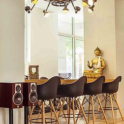 Der Esstisch mit 8 Barhockern und einer auffälligen Deckenlampe.