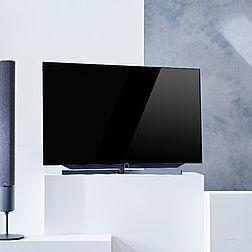 Loewe Bild 7 OLED TV an einer bunten Wand hängend.