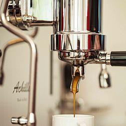 Die Quickmill Espressomaschine in Großaufnahme. Aus dem Siebträger läuft cremiger Espresso in eine weiße Tasse.