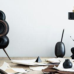 Ein Podspeaker Minipod in schwarz steht auf einem vollen Schreibtisch
